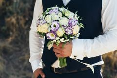 Beautiful bridal bouquet in hands of the groom. Wedding bouquet of white roses, hypericum, lisianthus, chrysanthemum, eustoma Royalty Free Stock Images
