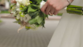 Beautiful bridal bouquet in hands of young bride dressed in white wedding dress. Close up of big bunch of fresh white roses flowers in female hands stock footage