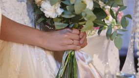Beautiful bridal bouquet in hands of young bride dressed in white wedding dress. Close up of big bunch of fresh white. Roses and tulips flowers in female hands stock footage
