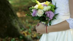 Beautiful bridal bouquet in hands of young bride dressed in white wedding dress. Close up of big bunch of fresh white. Roses and tulips flowers in female hands stock video footage