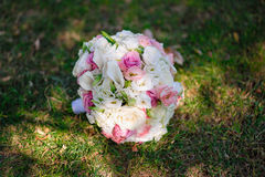 Beautiful bridal bouquet lying on the grass Royalty Free Stock Photo