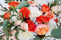 Beautiful bridal bouquet made of white and orange flowers. Ribbon and eucalyptus leaves Stock Photo
