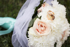 Beautiful bridal bouquet of roses with the wedding rings on it o Royalty Free Stock Photo