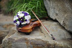 Beautiful bridal bouquet and violin on the rock Stock Images