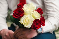 Beautiful bridal bouquet of white and red roses in the hands of the groom. Close up stock photos