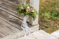 Beautiful bridal bouquet  whith ribbons and lace. Bridal bouquet with pink and white colors. Flowers in a rustic style, wedding bouquet on the steps of the manor Royalty Free Stock Photos