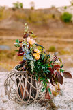 The Beautiful bridal bouquet on a wooden stand outdoors. Wedding floristic decoration. Royalty Free Stock Photos
