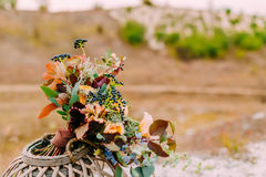The Beautiful bridal bouquet on a wooden stand outdoors. Wedding floristic decoration. Royalty Free Stock Image