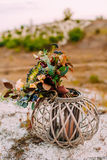 The Beautiful bridal bouquet on a wooden stand outdoors. Wedding floristic decoration. The Beautiful bridal bouquet on a wooden stand outdoors. Wedding Stock Photo