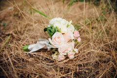 Beautiful bridal bouquet on a yellow grass Royalty Free Stock Photo