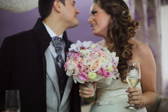 Beautiful bridal couple with bouquet of flowers and champagne Stock Photography