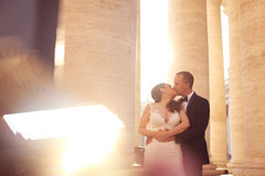 Beautiful bridal couple embracing and kissing near columns Royalty Free Stock Photos
