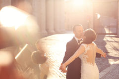 Beautiful bridal couple embracing and kissing in old city Royalty Free Stock Images