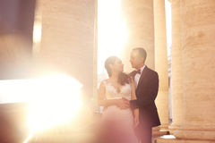 Beautiful bridal couple embracing near columns Stock Photography