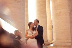 Beautiful bridal couple embracing near columns Royalty Free Stock Photos