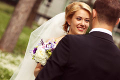 Beautiful bridal couple having fun in the park on their wedding day flower bouquet Stock Photo