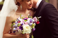 Beautiful bridal couple having fun in the park on their wedding day flower bouquet