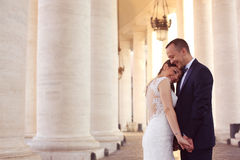 Beautiful bridal couple holding hands near columns Stock Photography