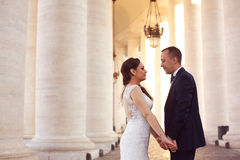 Beautiful bridal couple holding hands near columns Stock Photo