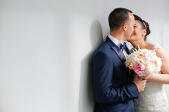 Beautiful bridal couple kissing next to white wall Stock Photos