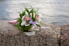 Beautiful bridal flower. Wedding bouquet on granite parapet with the background from water Royalty Free Stock Photo