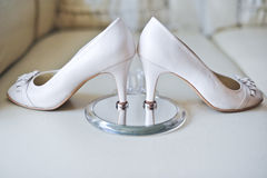 The beautiful bridal shoes and wedding rings Stock Images