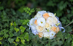 Beautiful bridal wedding bouquet lying on the grass Stock Photos