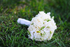 Beautiful bridal wedding bouquet lying on the grass Royalty Free Stock Image