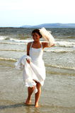 Beautiful Bride. A bride, dipping her toes in the sea, while holding up her dress and veil stock photos