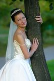 Beautiful bride. Portrait of the beautiful bride worth near a tree Royalty Free Stock Photos