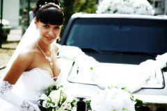 Beautiful bride. Woman with limousine on the background outdoors stock images