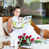 Beautiful bride. Sitting and reading magazine about golf Royalty Free Stock Image