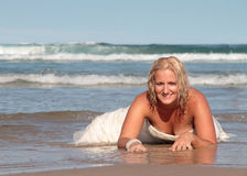 Beautiful Bride 2. Bride lays on the beach in a pose royalty free stock image