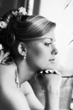 Beautiful bride. The beautiful sad bride looks in a window. b/w royalty free stock photos