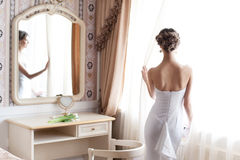 Beautiful bride. In white wedding dress standing in her bedroom near the window Stock Image