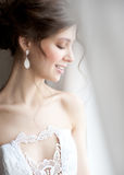 Beautiful bride. Standing near the window and smiling Royalty Free Stock Photos