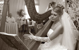Beautiful bride. The bride plays on a string musical instrument Royalty Free Stock Photos