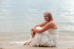 Beautiful Bride 4. Bride sits on the beach in happy reflection of her wedding day royalty free stock image