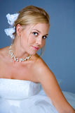 Beautiful bride. A portrait of a beautiful bride in white dress, on blue studio background Royalty Free Stock Photography