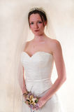 Beautiful Bride. Female model in a wedding gown standing very confidently holding her bouquet Stock Photo