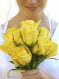 Beautiful bride. Smiles as she holds yellow roses in her hands Stock Photography