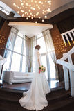 Beautiful bride against a big window indoors. Beautiful bride in white wedding dress standing on stairs and looking in the window . Fisheye lens Royalty Free Stock Images