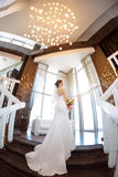 Beautiful bride against a big window indoors. Beautiful bride in white wedding dress standing on stairs near the window. Fisheye lens Royalty Free Stock Image