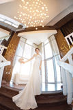 Beautiful bride against a big window indoors. Beautiful bride in white wedding dress standing on stairs near the window. Fisheye lens Stock Image