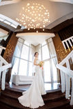 Beautiful bride against a big window indoors. Beautiful bride in white wedding dress standing on stairs near the window. Fisheye lens Stock Photos
