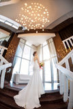 Beautiful bride against a big window indoors. Beautiful bride in white wedding dress standing on stairs near the window. Fisheye lens Royalty Free Stock Photos
