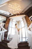 Beautiful bride against a big window indoors. Beautiful bride in white wedding dress standing on stairs near the window. Fisheye lens Stock Images