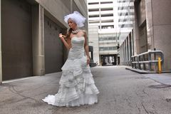 Beautiful bride in an alleyway. Beautiful caucasian blonde in a lovely wedding gown with veil in an alleyway Stock Images