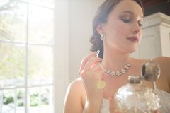 Beautiful bride applying perfume while standing by window. At home Royalty Free Stock Photos
