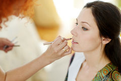Young beautiful bride applying wedding make-up Stock Photos
